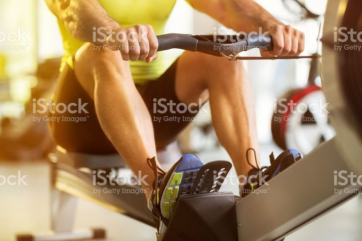 man training on row machine in gym royalty-free stock photo