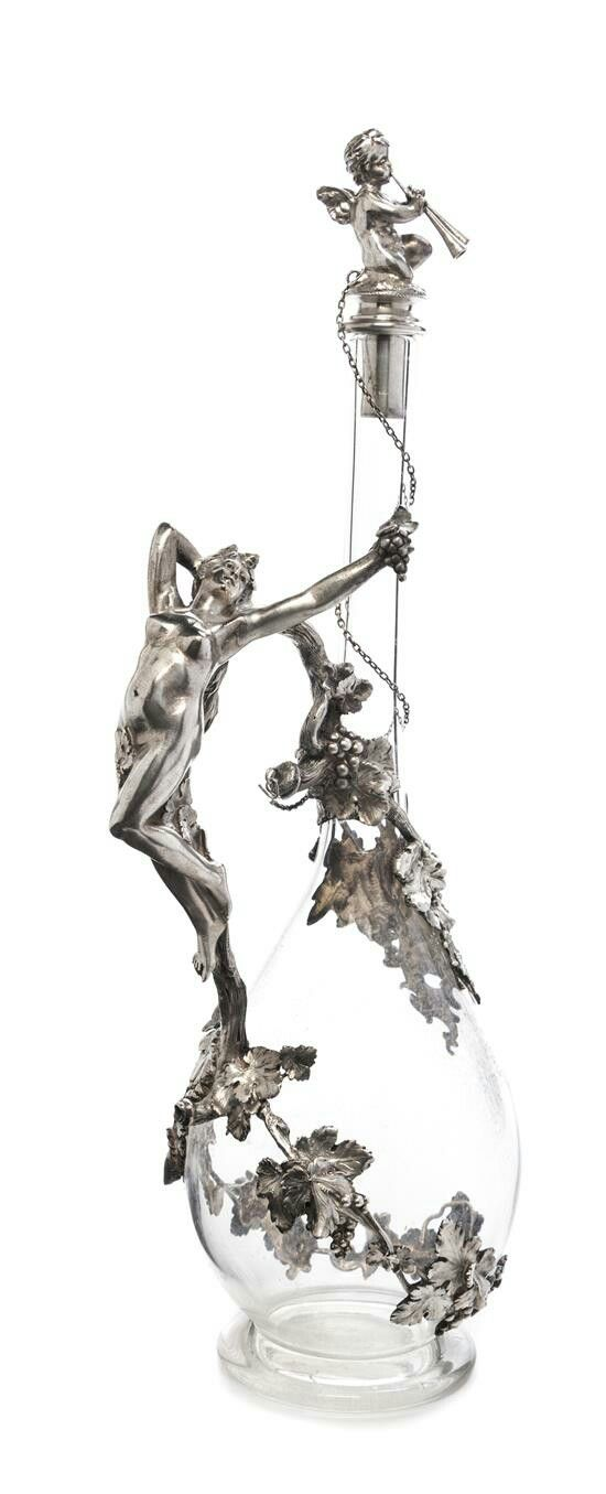 A German Silver Mounted Cut Glass Decanter  Bruckmann & Sohne, Heilbronn, Circa 1910  having a figural stopper in the form of winged putto playing a syrinx, the handle formed as a Bacchante joined to the body with grapevines, monogrammed within a rococo cartouche on one side.  Height 15 1/2 inches.