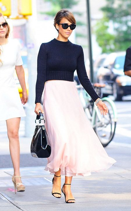 Модель в легкой нежно розовой длинной юбке и черном укороченном свитере