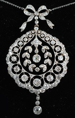 An Edwardian diamond and platinum pendant, circa 1910, with an articulated bow…