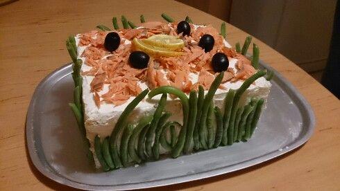 Slaný dort s lososem, fazolkami a olivami. Promazaný cesnekovou a bazalkovou pomazánkou spolu s kolečky okurky.