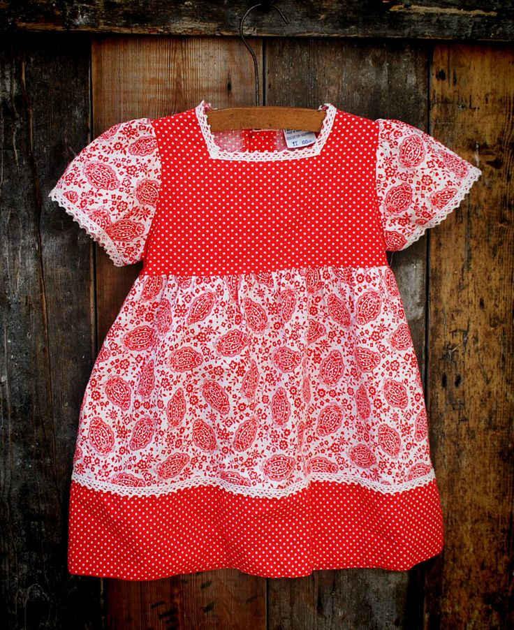 1970S PATTERNED AND POLKA DOT DRESS  12.00 1970's Red patterned and polka dot dress approx. age 1-2 years  Delightful little red cotton dress made up of floral and polka dot patterned fabric, with cap sleeves and lace trim. The dress is fastened with buttons and a ribbon tie at the back. Made by Mothercare