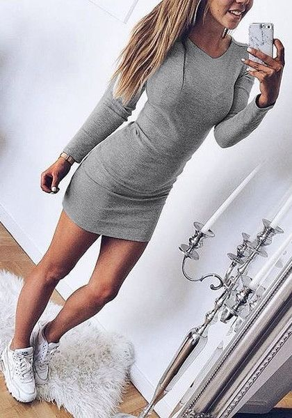 Angled view of model in grey long sleeve bodycon dress