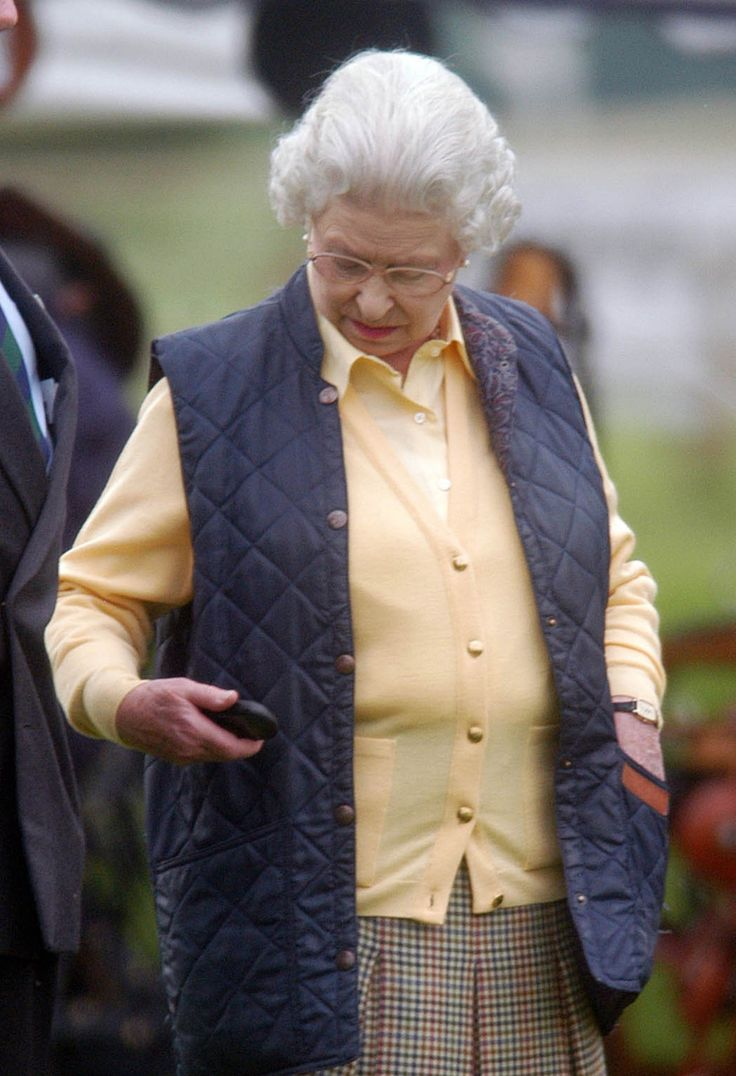 Queen Elizabeth pictured with her mobile phone for the first time at the Royal Windsor Horse Show, 2004.