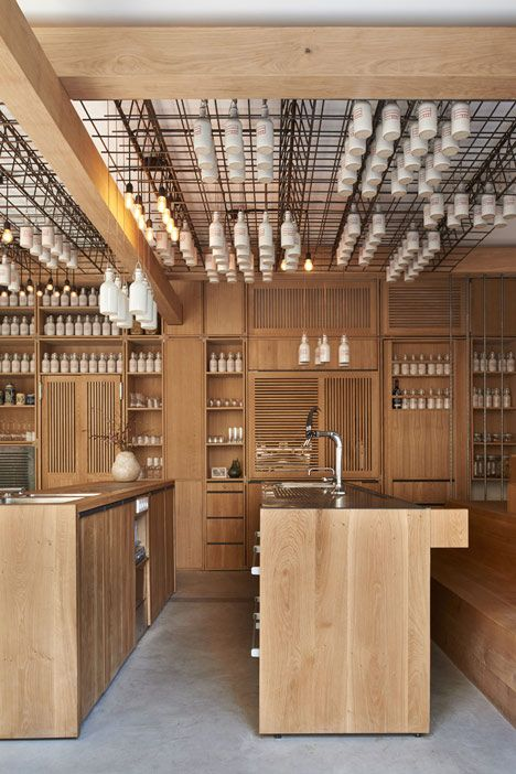 German firm Buero Wagner has designed a bar for mixology company Gamsei with ceramic bottles of ingredients hanging from a metal grid on the ceiling