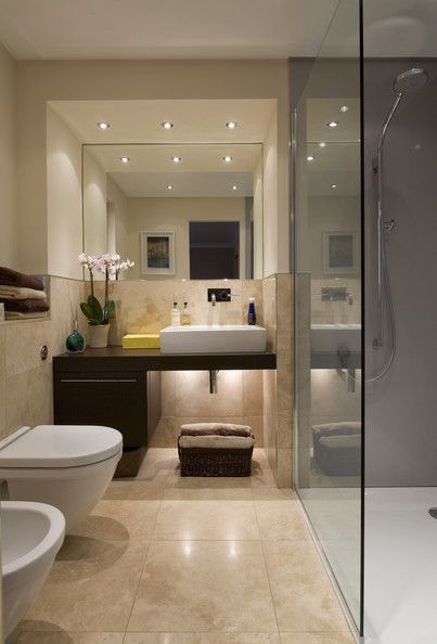 a modern bathroom which has been designed by the neutral tile colourthe mirror and the dark wood