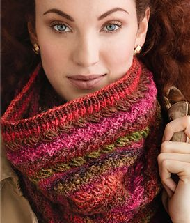 This standout cowl flaunts strips of slanted stitches dotted with eyelets for a unique openwork pattern.