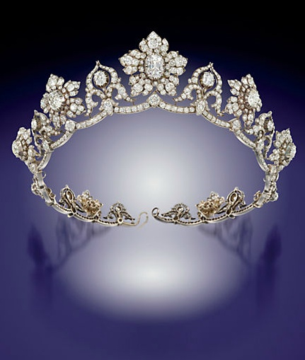 A MID-19TH CENTURY DIAMOND TIARA. Composed of a series of nine old-cut diamond graduating flowerhead clusters centred by old-cut pear and cushion shape diamond collet highlights, interspersed by ten similarly-set stylised Toy cusp motifs of ribbon scroll design, raised on an undulating diamond line frame, mounted in silver and gold, circa 1850. Each flowerhead cluster detaches to form a brooch. (Christie's)