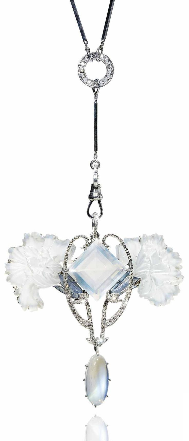 RENÉ LALIQUE - AN ART NOUVEAU MOONSTONE, DIAMOND, ENAMEL AND GLASS PENDANT, 1904-05. Centring a square-cut moonstone, between two opalescent glass carnations with enamel and diamond stems, suspending an oval cabochon moonstone, the chain with diamond accents, with French assay marks for platinum, pendant signed Lalique, chain signed G. Fouquet.