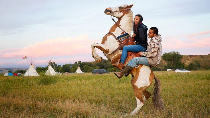 Stevana Salazar (links) van de Kickapoo stam van Texas rijdt met Arlo Standing Bear, Oglala Lakota van Allen (South Dakota). Paarden zijn alomtegenwoordig in het kamp, zoals renners de vrede te bewaren, scout voor activiteiten op de pijpleiding en deelnemen aan wedstrijden en spelletjes.