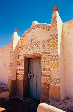 """While many motifs recur frequently, the differences in decoration from one house to another are often lively. The home at right has an all-geometric decoration. Much of the Nubian style is attributed to a builder-artist of the early 20th century named Ahmad Batoul, whose iconography has become """"traditional."""""""