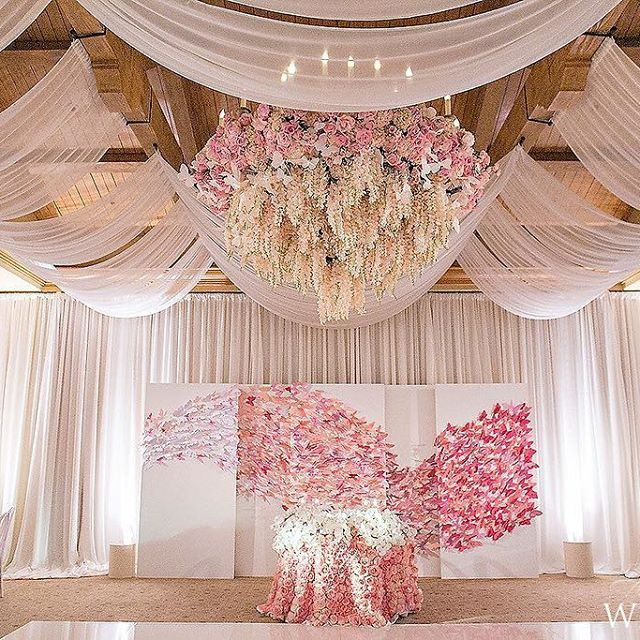 The focal point of this wedding-reception was the backdrop of the newlyweds' sweetheart table, covered in thousands of ombre paper butterflies. It perfectly complemented the massive floral chandelier draped with hanging wisteria. | WedLuxe Magazine