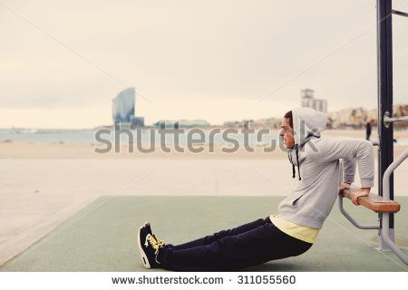 Side view portrait of strong man doing muscles exercises on training apparatus outdoors, fit man pumps biceps at seashore horizontal bar, sportsman at physical activity in cloudy cold morning, filter