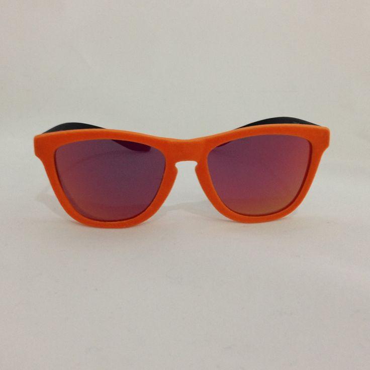 Occhiale da sole centro style modello Koala con frontale arancione in velluto e aste nere, lenti specchiate polarizzate di colore blu sfumate. Occhiali alla moda, unisex con montatura composta da materiale Iniettato propionato. L'occhiale Centro Style è caratterrizato da aste lunghe e flessibili, facili da portate al collo o tra i capelli senza danneggiarsi o allargarsi minimante. L'occhiale assume le sembianze del modello Oakley Frosgkyns.   http://www.cheocch