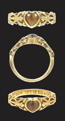 Decorated gold ring with wolf's tooth set in a heart-shaped bezel, made between 1200-1300 in France or England, inscription added around 1375-1425. Inside the hoop are two engravings: a magic formula and a biblical phrase. The charm: 'BURO+BERTO+BERNETO' is to protect against toothache; the biblical phrase 'CONSUMMATUM+EST' are the last words Christ spoke on the Cross, and were used as a charm to calm storms. This large ring likely belonged to a man. (V&A museum, item 816-1902, London, UK).
