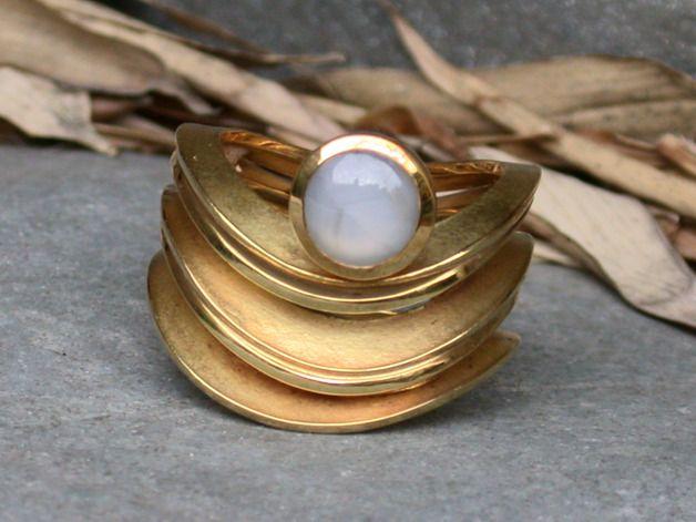Skulpturaler goldener Ring mit einem blau-grauen Sternsaphir. Der Ring besteht aus einzelnen goldenen Scheibchen, die an auf den Strand laufende Wellen erinnern. Der Saphir zeigt unter einer...
