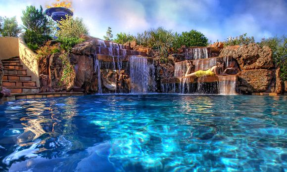Backyard swimming pool with beautiful waterfalls made by for Beautiful house designs with swimming pool