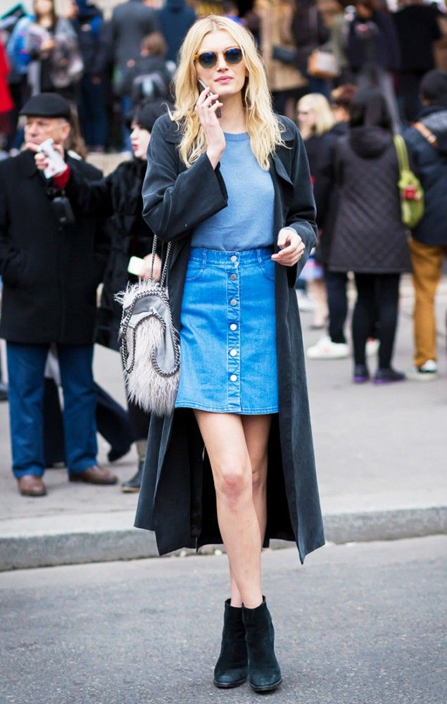 Lily Donaldson in a button up denim skirt, cape, and black booties: