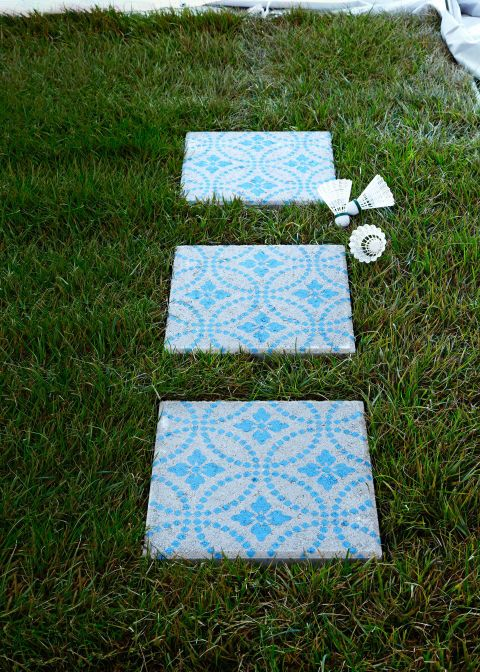 To brighten up a plain concrete patio stone, first brush away any debris. Then, mark the centers of the stone and your stencil. Position the stencil over the stone, aligning the center marks. Use masking tape to block off two flowers on both the right and bottom edges of the stencil to make the pattern symmetrical. Paint with Chalk Paint. When you're done, remove the stencil. That's it—no sealer necessary!
