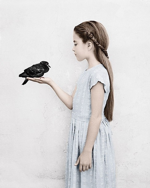 Girl holding a bird in her hand