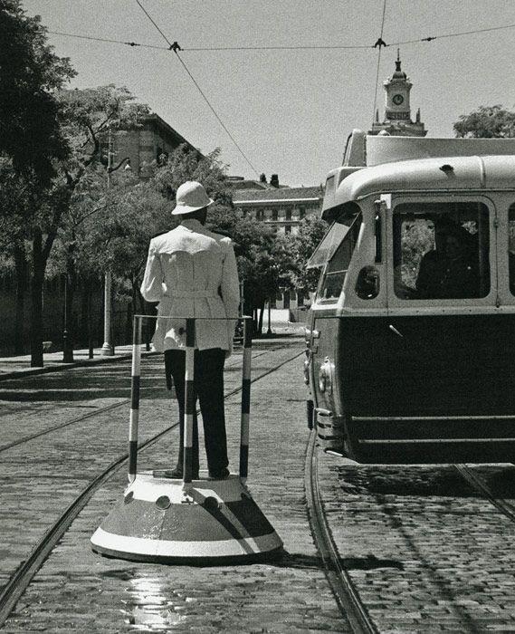 1953. Tocados con sus clásicos salacots, este guardia urbano gestiona su cruce entre las vías del tranvía.