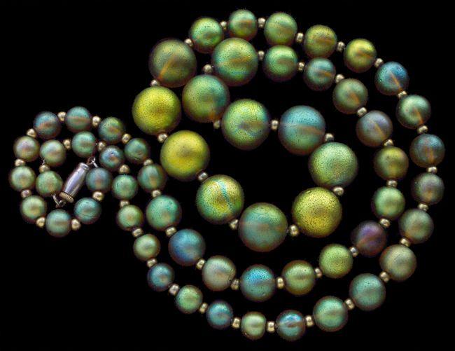 WÜRTTEMBERGISCHE METALLWARENFABRIK (WMF) Fabulous Iridescent Glass Bead Necklace  Glass Metal H: 1.4 cm (0.55 in)  W: 75 cm (29.53 in)  German, c.1930 This is an unusually long string of 60 wmf graduated beads Literature: cf. Schmuck der 20er und 30er Jahre in Deutschland, Christianne Weber, p. 354 no 806