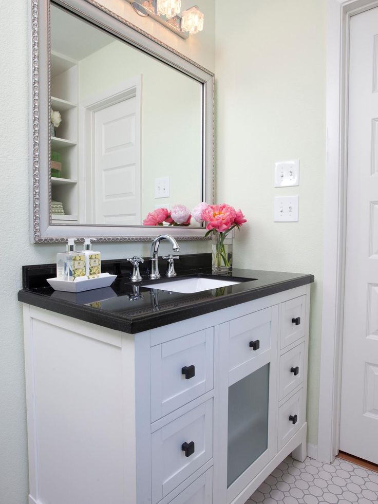 A black and white vanity with a polished black countertop has plenty of counter space with an under-mounted sink for easy cleanup. The octagonal tile and decorative mirror finish the room.