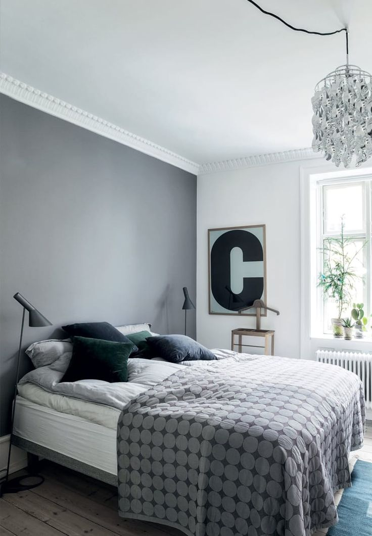 The bedroom is kept in gray, blue and green tones added warm wood. The bedspread is from Hay and the velvet pillows are from Magazine and Ikea.