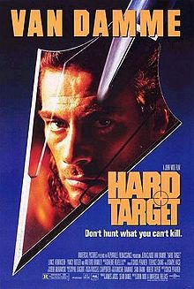 """Film poster with a gradient background fading from black to blue. In the middle is the head of an arrow with the character Chance's reflection in it. At the top of the poster is the name """"Van Damme"""" in capital letters. At the bottom left corner is the film's title, production staff and cast and catch slogan stating """"Don't Hurt What You Can't Kill""""."""