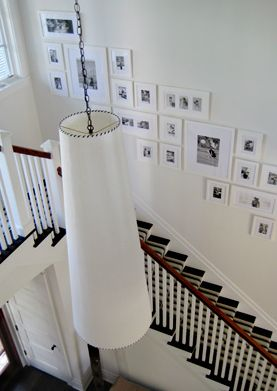 source: S. Russell Groves  Black & white stair photo gallery, white tapered pendant light and striped black & white stair runner. white black entrance foyer colors.