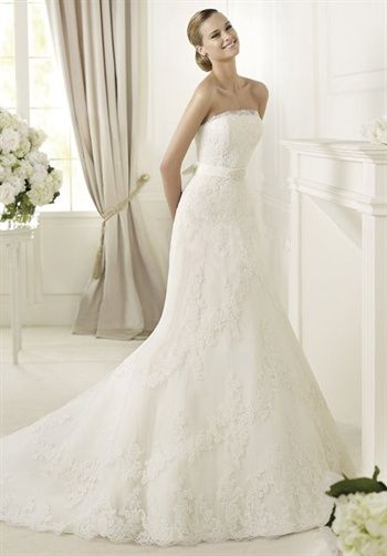 Elegant brides will find everything they have ever dreamed of in the Danesa model from the Pronovias 2013 collection. This lace over tulle creation has very restrained lines. The strapless neckline has an original tulle edging that echoes the lace on the skirt and bodice. A narrow belt encircles the waist, finishing in a bow at the back and has elegant embroidery at the front.