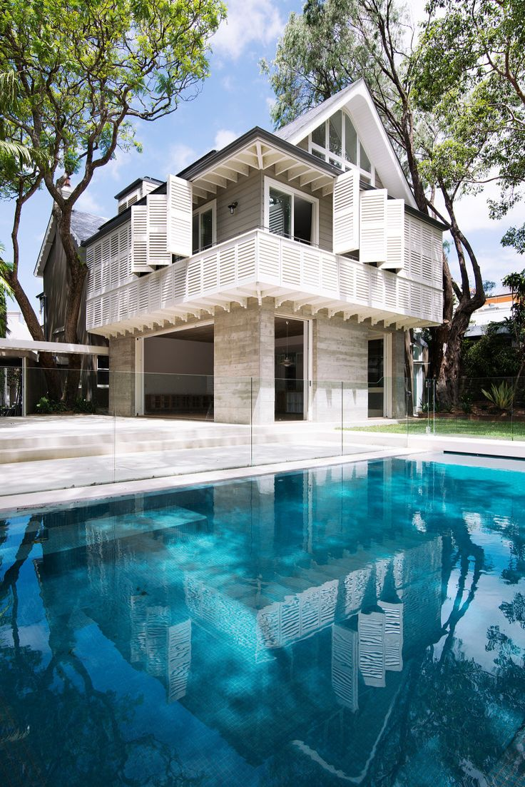 A flush edge swimming pool reflects the retractable and tilting shutters of the first floor balcony.  The addition is designed to create the most compact footprint and preserve the garden and courtyard space. © Edward Birch
