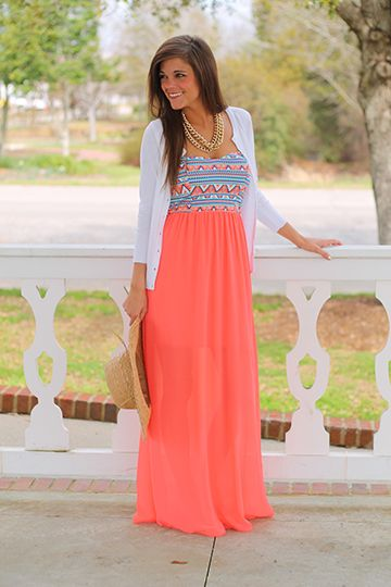 """Tribal Sensation Maxi, Coral $41.00 How fabulous is the pattern on the bodice of this maxi?! The colors are perfect for the warm weather, and we love the sheer coral skirt that is lined to just above the knee. Miranda paired this with a gold necklace and white cardigan! Fits true to size. Miranda is wearing a small. From shoulder to hem: Small - 52"""" Medium - 52.5"""" Large - 53"""""""