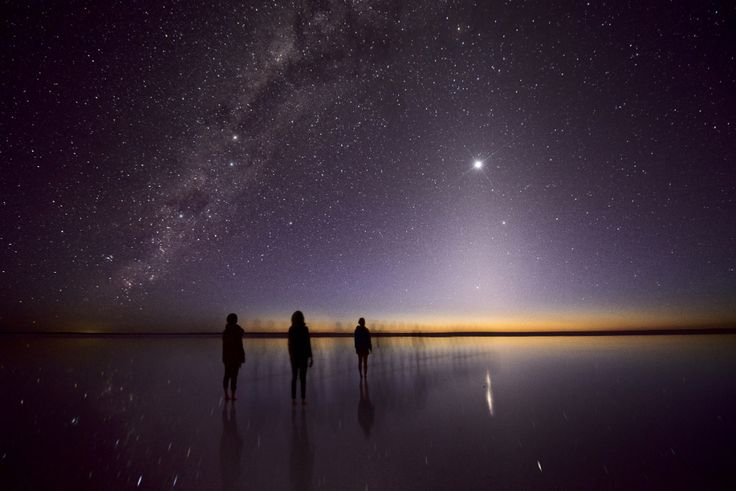 Julie Fletcher of Australia composed this evocative image of human figures below a triangle of zodiacal light with Venus at the apex. The temporary waters of Kati Thanda-Lake Eyre below reflect the people. Zodiacal light is produced by sunlight reflecting on dust floating between the planets in the plane of the solar system. Read the Full Story Here.