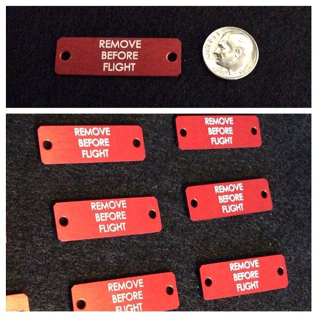 Dime sized red anodize aluminum part with two small holes and laser engraving