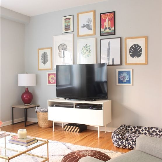 My living room is a mixture of mid-century modern and glam. I have the IKEA RAMSÄTRA TV stand and a couple IKEA frames on the gallery wall. The basket is also from IKEA. With such a large TV, I wanted to create a gallery wall with some larger art to make it seem not as big. More photos: http://www.designevolving.com/home-tour/