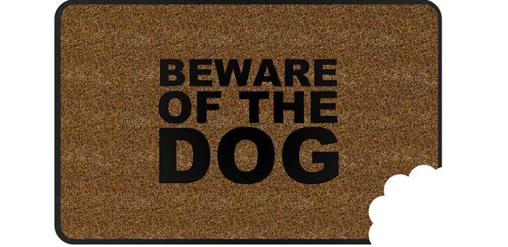 """Antes de entrar en casa, lo primero que se ve es el felpudo. ¿Por qué no poner uno bien original? Aquí lo tienes: """"Cuidado con el perro"""" en inglés. Con un mordisco a juego."""