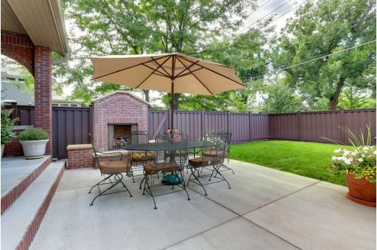Gorgeous patio with outfoor fireplace and bright green grass.