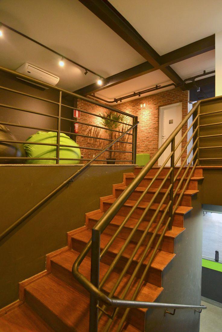 Academia CrossFit BH 3 - Paredes em quadro negro e tijolo aparente. Escada de acesso ao estar em madeira. Instalações e estrutura aparentes pintados de preto em estilo industrial. Corrimão em esmalte preto