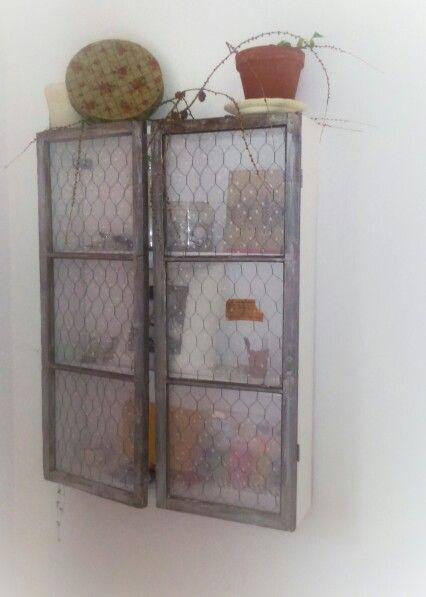 Ett skåp gjort av gamla fönster och hönsnät,  nu har det blivit adventspyntat med lärkgrenar.