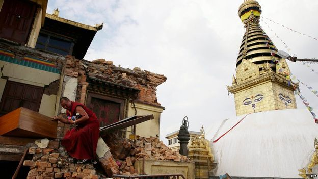 A monk salvages belongings from the rubble at Nepalese heritage site Syambhunaath Stupa, also known as monkey temple, after a powerful earthquake struck Nepal (26 April 2015)