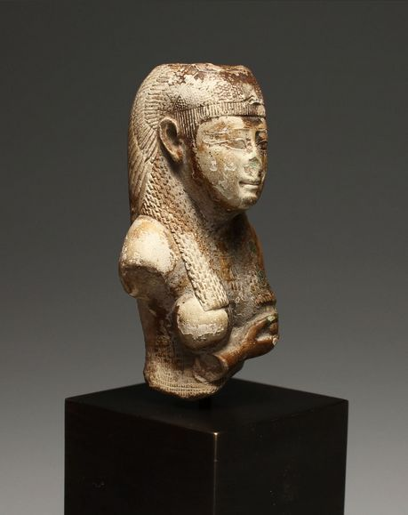 Egyptian Bust of Isis circa 26th-30th Dynasty, 664-332 B.C. Glazed composition, the goddess holding her right arm to her left breast to nurse Harpocrates, now missing, wearing a finely detailed tripartite wig with an ornate vulture headdress, wearing a broad collar, with an image of a falcon on her back. Old collection number on the underside. Although this is a fragment from a large figure, the details are superior in comparison to parallels.