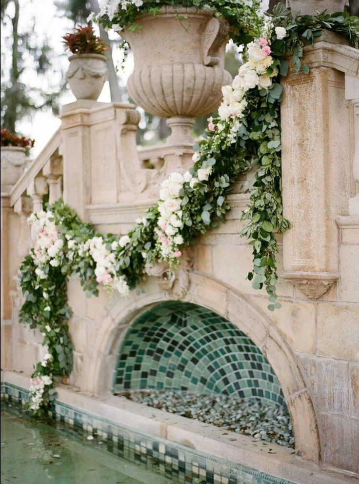 for the ceremony site, an asymmetrical lemon leaf and eucalyptus garland is hung over the stairwell fountain and is adorned with clusters of white O'Hara garden roses, Vendela roses, pink spray rose, white larkspur, pink carnations and white carnations.
