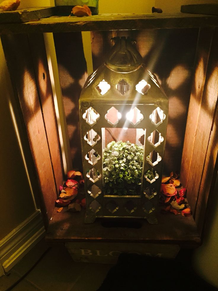 Vintage Apple crate placed as lantern shelf in corner.
