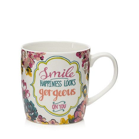 From At home with Ashley Thomas, this mug is a colourful update to a tableware collection. In white, it is finished with a floral 'happiness' motif.