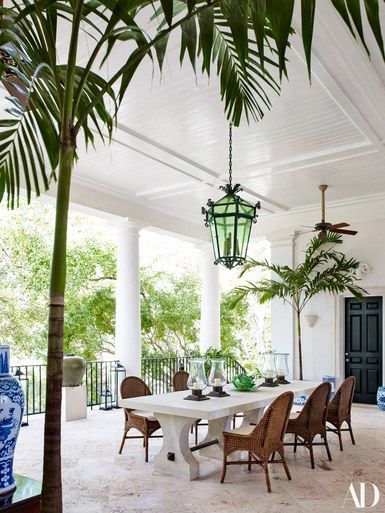 On the dining loggia, an antique wrought-iron lantern illuminates a french limestone table surrounded by wicker chairs | archdigest.com