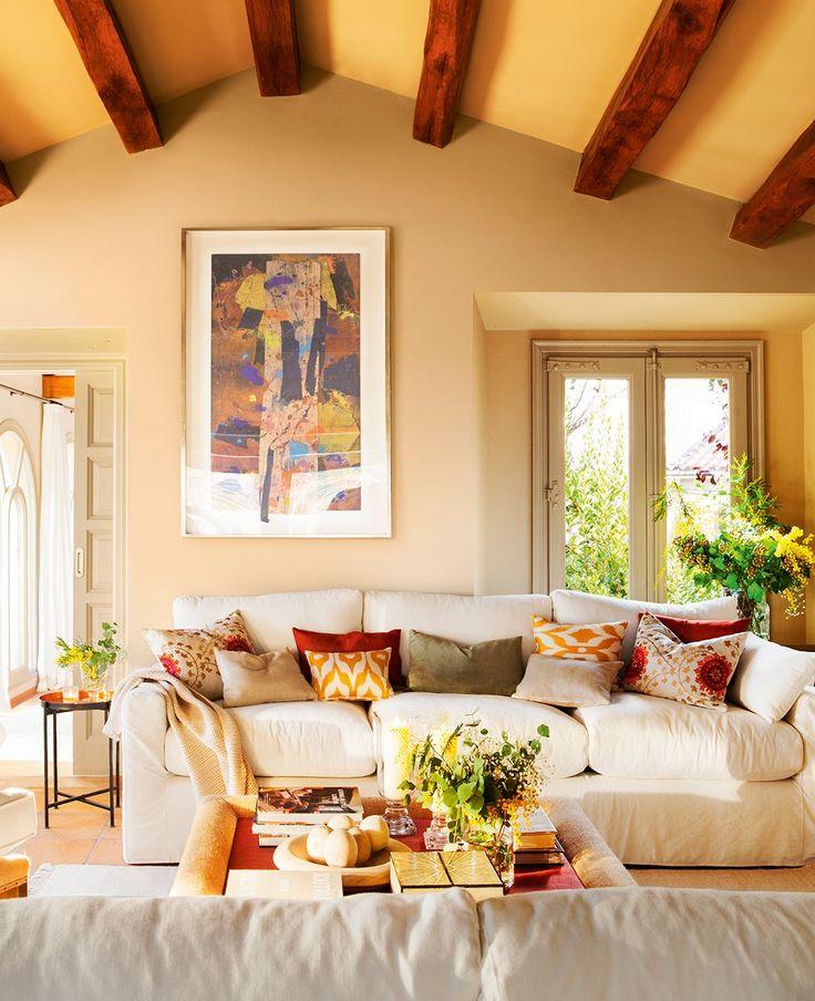 Rincón de estar con sofás blancos y cuadros abstractos