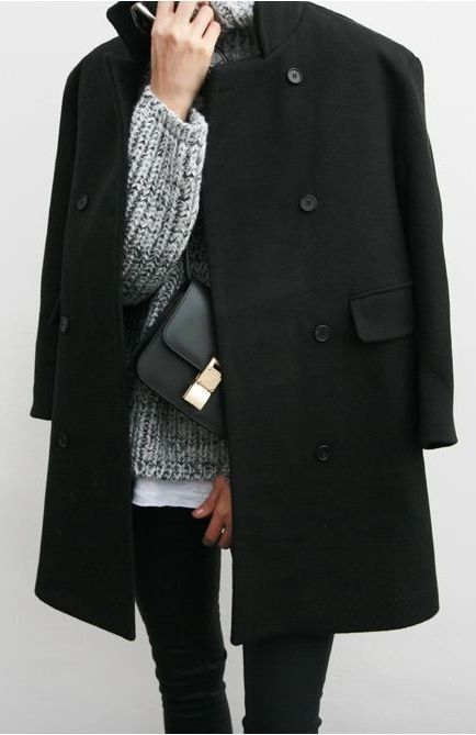 Black coat, grey turtleneck sweater, black jeans, and a gold and black cross body.