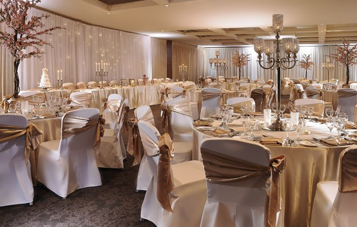 Spring Wedding Setting with cherry trees and candle lanterns and champagne table cloth and sash