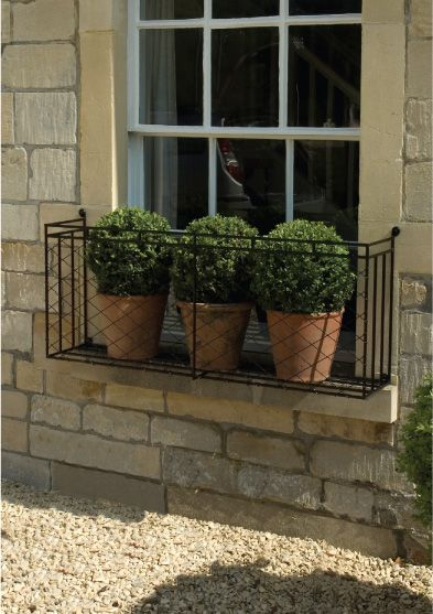 Windows/ wrought iron overhang...+ boxwood pots -- privacy yet provides view, bit of safer feeling, & changeable for seasons